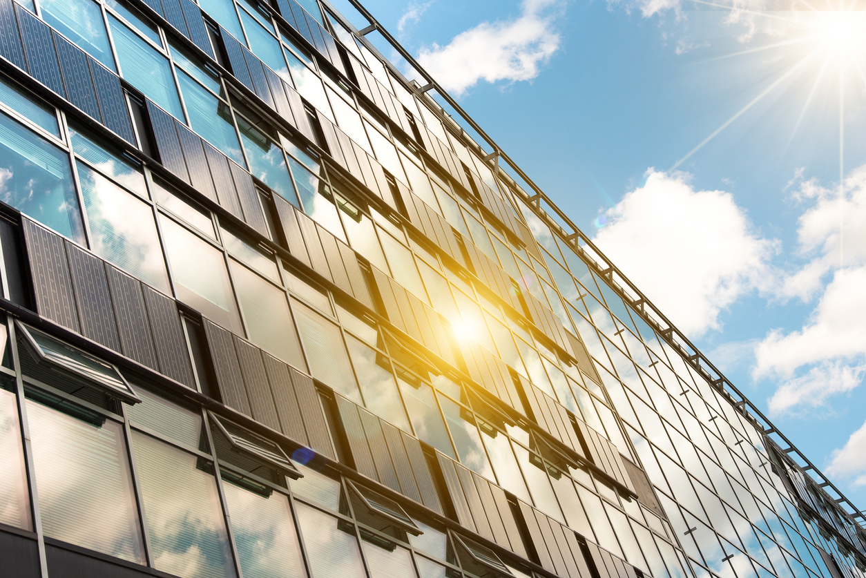 solar panels on modern glass facade with sun reflections